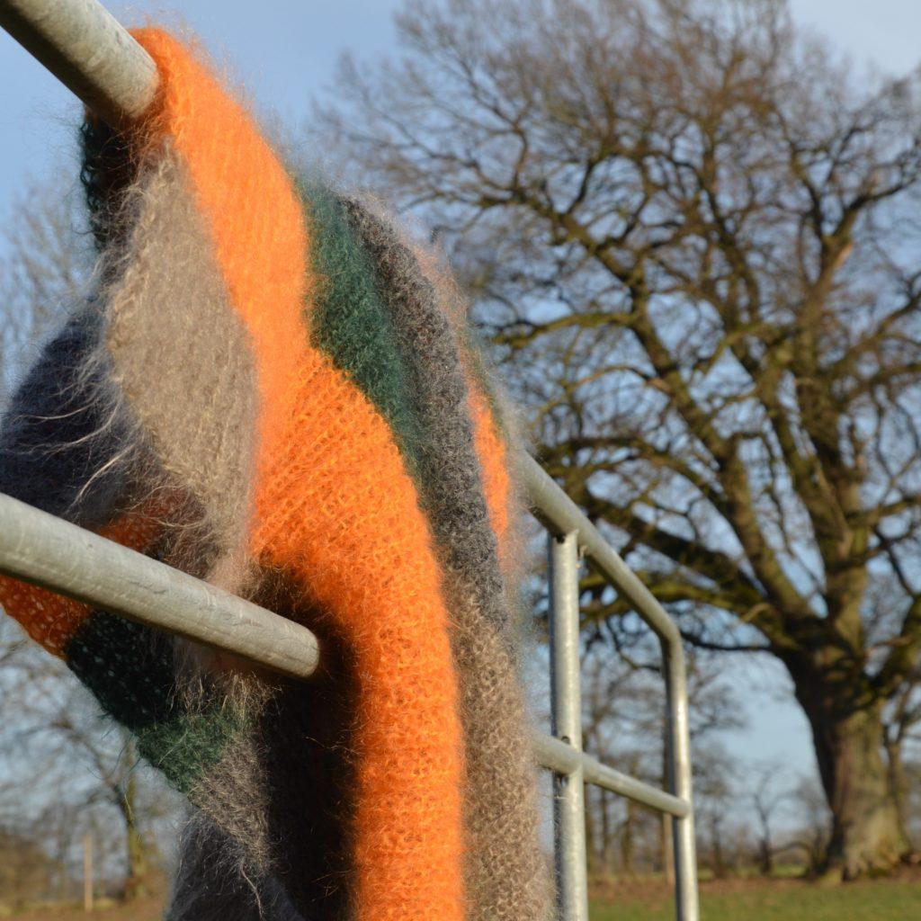 Eine Mohairwolldecke hängt über dem Gatter