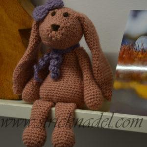 Ein kleiner gehäkelter Hase sitzt auf einem Regal.