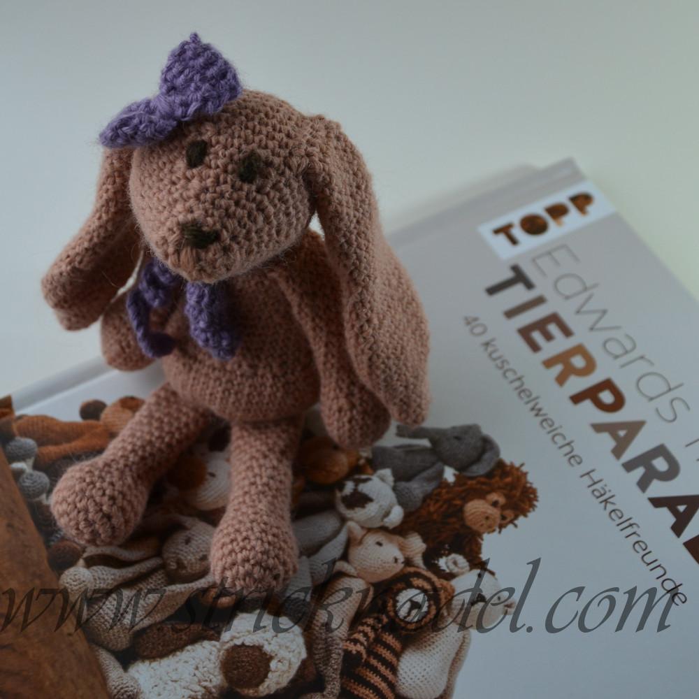 Eine kleine Kuschelhäsin sitzt auf einem Buch
