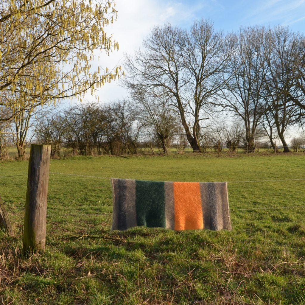 Eine Mohairwolldecke hängt über dem Zaun