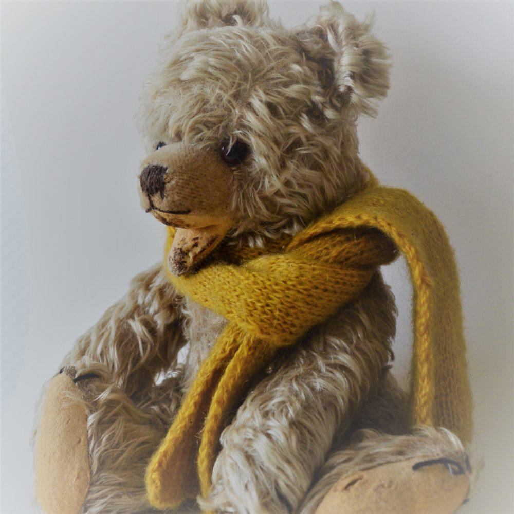 Ein alter Teddybär mit einem gelben selbstgestrickten Schal.