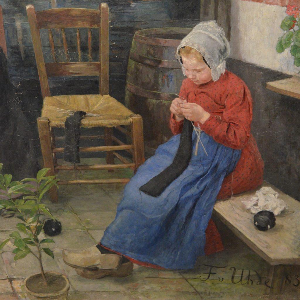 Ein junges Mädchen sitzt strickend auf der Bank vor dem Haus