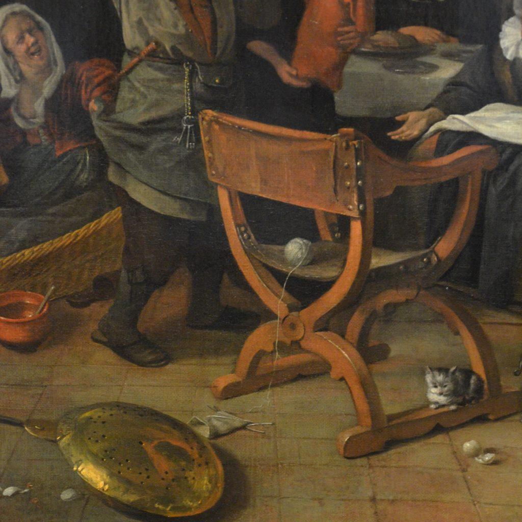 Ein Strickstrumpf liegt auf dem Boden, die Wolle auf der Sitzfläche des Stuhles
